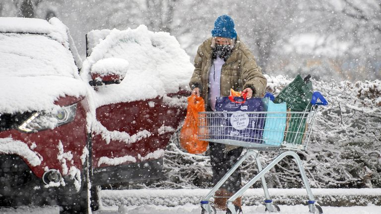A woman loads shopping into her car as heavy snow falls in Dunstable, Bedfordshire