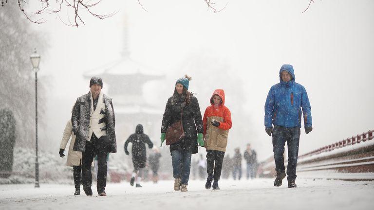 People walking in the snow in Battersea Park, London