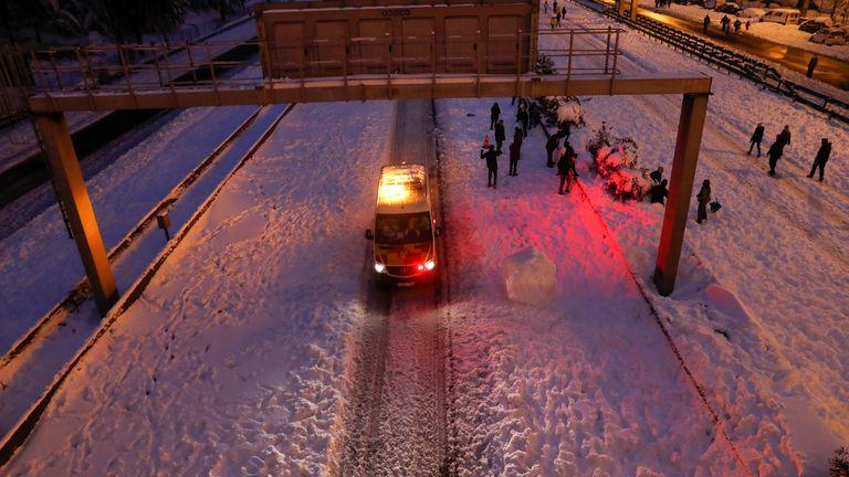 An emergency vehicle drives past people walking in the snow on the M-30 motorway, in Madrid, Spain, January 9, 2021. REUTERS/Susana Vera