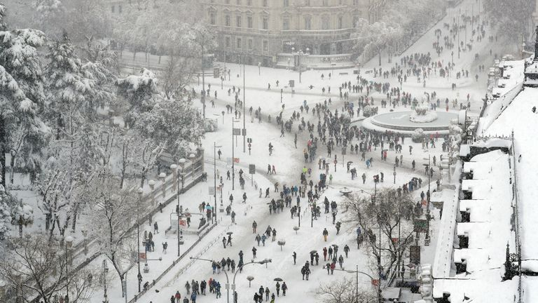 People are seen from the rooftop of the Circulo de Bellas Artes cultural center, as they stand and walk near the Cibeles Fountain during a heavy snowfall in Madrid, Spain January 9, 2021. REUTERS/Susana Vera