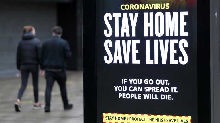 People walk past a 'Stay Home Save Lives' government sign on Commercial road in Portsmouth