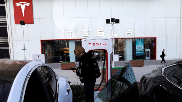 A woman charges a Tesla car in front of the electric vehicle maker's showroom in Beijing, China January 5, 2021