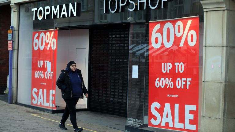 A woman walks past a closed Topman/Topshop store in Loughborough, Leicestershire during England's third national lockdown to curb the spread of coronavirus.