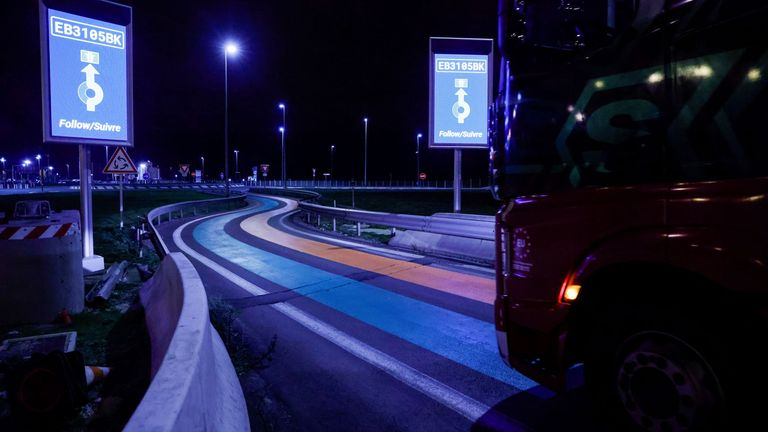 A truck drives over green and orange lines on the road that are part of the new customs infrastructure for entry into France, in Calais, France, January 1, 2021. REUTERS/Pascal Rossignol