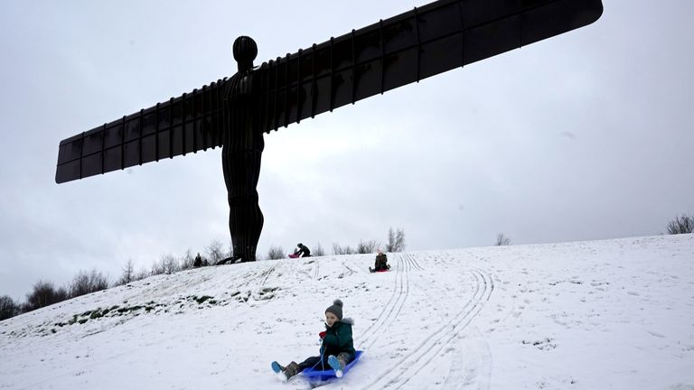 Sledgers have fun in the snow surrounding the Angel of the North near Gateshead, Tyne and Wear.