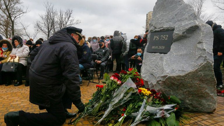 A pilot lays flowers to a memorial in Kyiv, Ukraine, Friday, Jan. 8, 2021, for the victims of a Ukrainian 737-800 plane crash on the outskirts of Tehran. (AP Photo/Efrem Lukatsky)