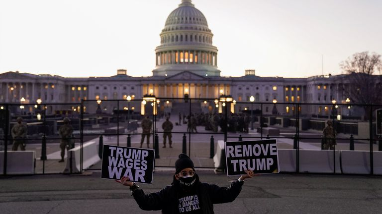 A protester holds signs near the US Capitol calling for the removal of Mr Trump