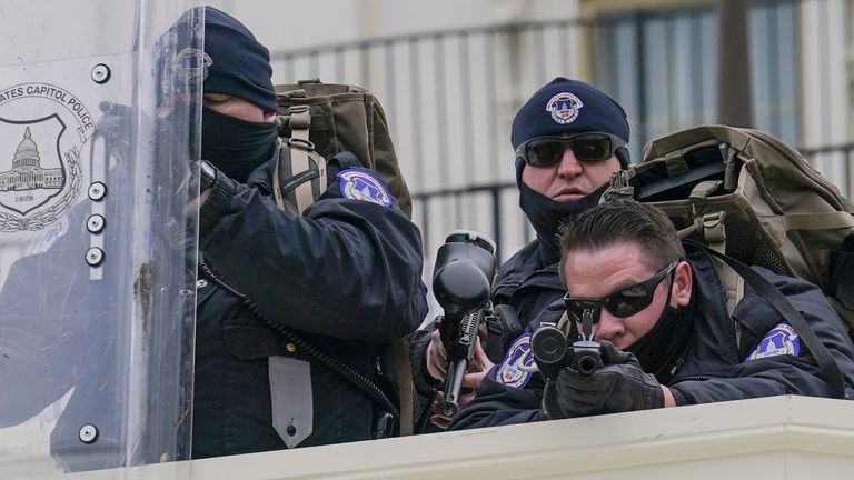 Police keep a watch on demonstrators who tried to break through a police barrier, Wednesday, Jan. 6, 2021, at the Capitol in Washington. As Congress prepares to affirm President-elect Joe Biden's victory, thousands of people have gathered to show their support for President Donald Trump and his claims of election fraud.(AP Photo/John Minchillo)