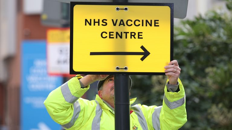 A Brent Council worker hangs a direction sign to the NHS Covid Vaccine Centre at the Olympic Office Centre, Wembley, north London, as ten further mass vaccination centres opened in England with more than a million over-80s invited to receive their coronavirus jab. Picture date: Monday January 18, 2021.