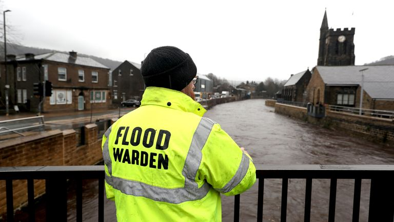 A flood warden inspects River Calder water levels in Mytholmroyd, West Yorkshire
