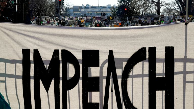 """A protest sign reading """"Impeach"""" is seen on Black Lives Matter Plaza near the White House one week after rioters stormed the U.S. Capitol building in Washington, U.S., January 13, 2021. REUTERS/Erin Scott"""