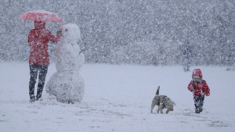 A woman builds a snowman during heavy snow fall in London. Pic: AP