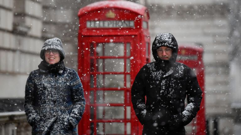 People walk through central London, as snow falls