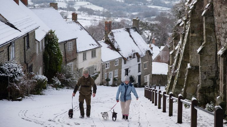 Dog walkers on a snowy Gold Hill, in Shaftesbury, Dorset