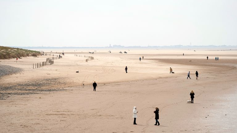 People stroll along the beach in Blackpool.