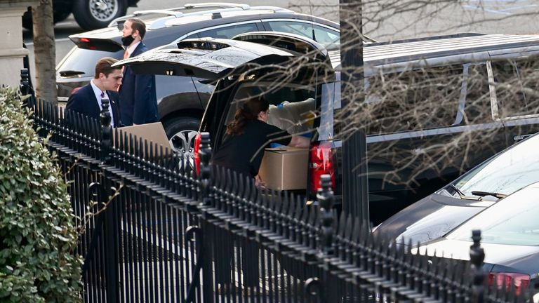 Boxes and other items from the West Wing of the White House are loaded into a car