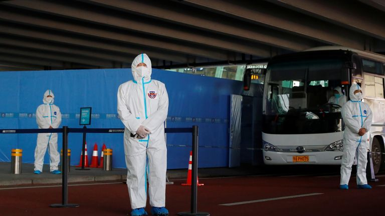Local officials at Wuhan Airport wait in protective suits for WHO officials to arrive