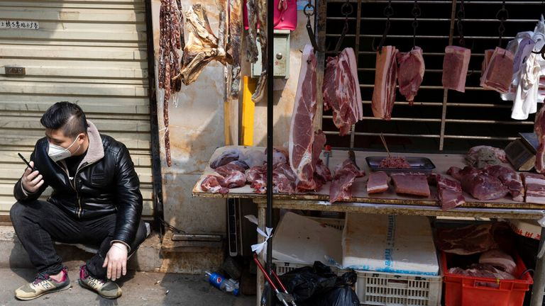 AP: In this photo taken Friday, April 3, 2020, a vendor waits for customers at a stall near a still partially closed off market due to the coronavirus outbreak in Wuhan in central China's Hubei province. (AP Photo/Ng Han Guan)