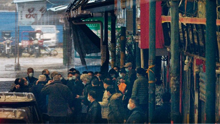 Members of the World Health Organization's team investigating the origins of the coronavirus pandemic arrive at the Huanan seafood wholesale market in Wuhan, China, on Jan. 31, 2021. (Kyodo via AP Images) ==Kyodo
