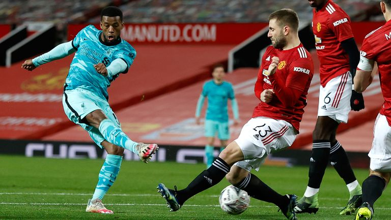 Georginio Wijnaldum has a shot on goal under pressure from Luke Shaw