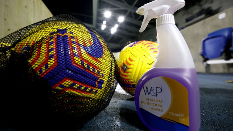 Premier League balls next to disinfectant spray
