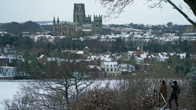 People take pictures from Pelaw Wood of a snow covered Durham Cathedral