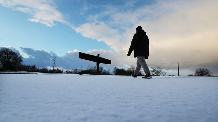 A member of the public is seen walking in the snow towards The Angel of the North in Gateshead, England, Monday, Feb. 8, 2021. Snow has swept across the region, with further snowfall predicted to impact on the country bringing travel problems as temperatures drop. (AP Photo/Scott Heppell)