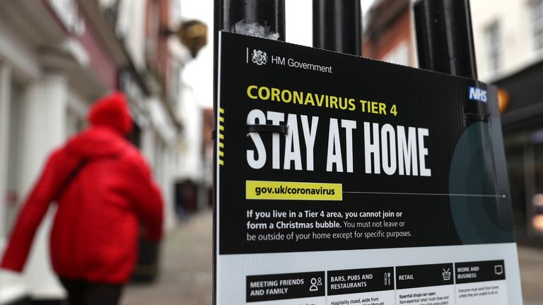 People make their way past a Government coronavirus Tier 4 sign on the High street in Winchester, Hampshire. Millions more people have moved to harsher coronavirus restrictions today as the new tier changes came into force in England.