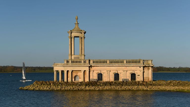 A person in a sailing dinghy passes Normanton Church at Rutland Water reservoir in Rutland.