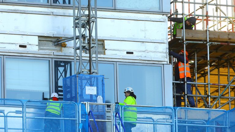 Workmen remove the cladding from the facade of a block of flats in Paddington, north London.