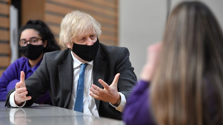 Prime Minister Boris Johnson speaks with Year 11 students in the canteen during a visit to Accrington Academy in Accrington, Lancashire, as they prepare for the return of all pupils on March 8. Picture date: Thursday February 25, 2021.