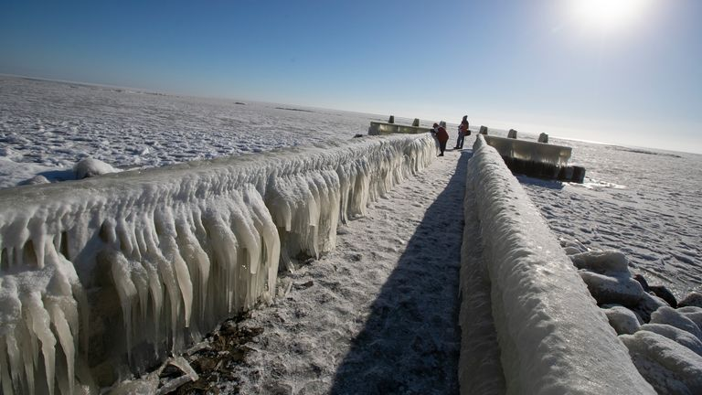 People take pictures of icicles on a jetty at the Afsluitdijk, a dike separating IJsselmeer inland sea, rear, and the Wadden Sea, Netherlands, Thursday, Feb. 11, 2021. The deep freeze gripping parts of Europe served up fun and frustration with heavy snow cutting power to some 37,000 homes in central Slovakia. (AP Photo/Peter Dejong)