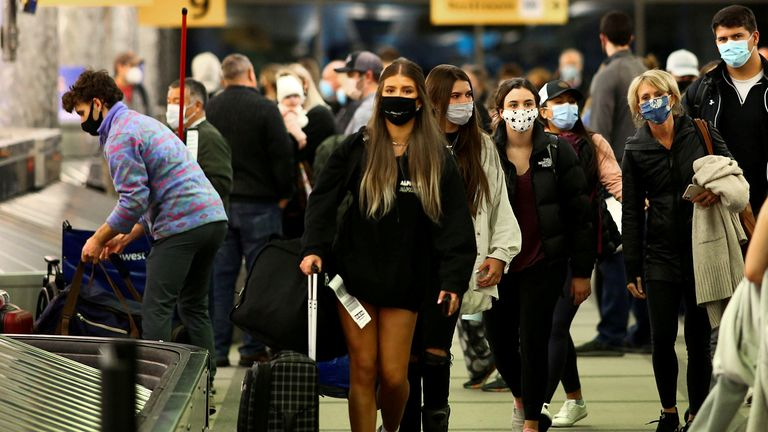 Travellers wearing protective face masks to prevent the spread of the coronavirus disease (COVID-19) reclaim their luggage at the airport in Denver, Colorado, U.S., November 24, 2020