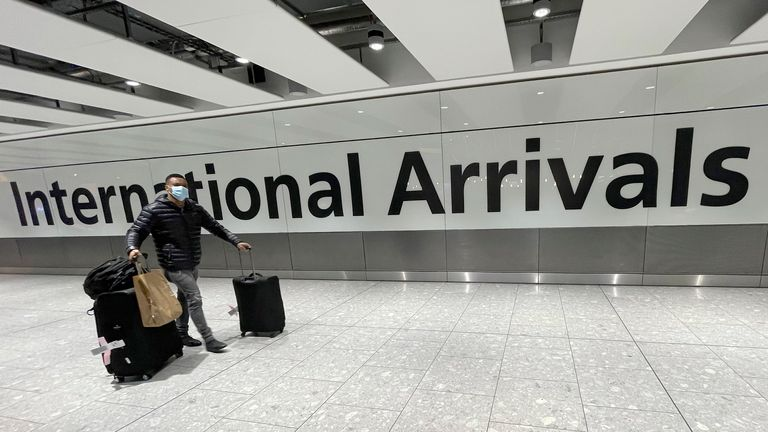Travellers arrive at Heathrow Airport in London, Sunday, Jan. 17, 2021. The UK will close all travel corridors from Monday morning to protect against the coronavirus with travellers entering the country from overseas required to have proof of a negative Covid test. (AP Photo/Frank Augstein)