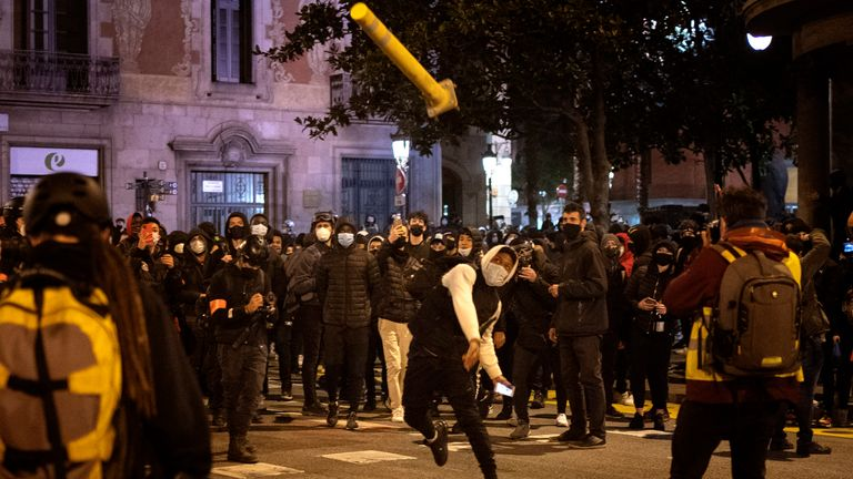 A protester throws a road sign at police during demonstrations in Barcelona. Pic: AP