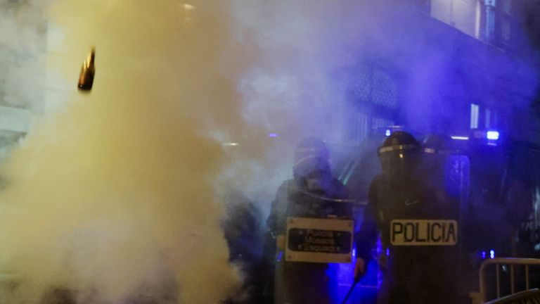 A bottle is thrown at police on Sunday in Barcelona on a sixth night of violent protests. Pic:AP