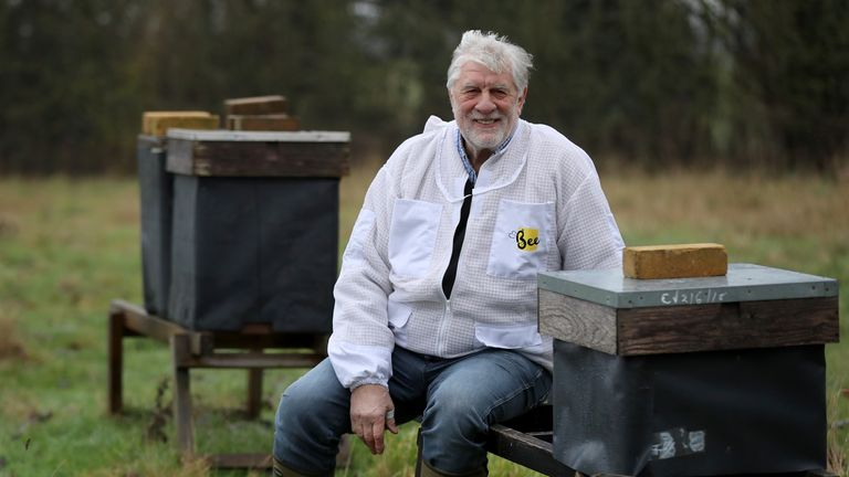 Beekeeper Patrick Murfet with some of his hives in an orchard near Canterbury