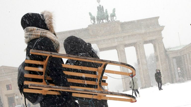 A pair carry their sledge near near Berlin's Brandenberg Gate