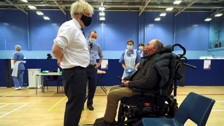 Boris Johnson speaks with a man as he waits to receive an Oxford-AstraZeneca COVID-19 vaccine, during his visit at a vaccination centre at Cwmbran Stadium in Cwmbran, south Wales
