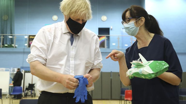 Prime minister Boris Johnson speaks with health worker Wendy Warren as he puts on a pair of medical gloves during a visit to a vaccination centre at Cwmbran Stadium in Cwmbran, south Wales