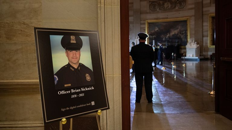 A picture of of Capitol Police officer Brian Sicknick, who died on Jan. 7 from injuries he sustained while protecting the U.S. Capitol during the Jan. 6 attack on the building, is seen as people wait for his remains to arrive to lay in honor in the Rotunda of the U.S. Capitol building in Washington, DC, U.S. February 2, 2021. Brendan Smialowski/Pool via REUTERS