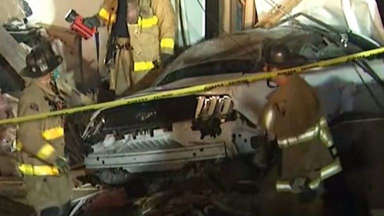 Emergency services survey damage after a car crashed into a home in California