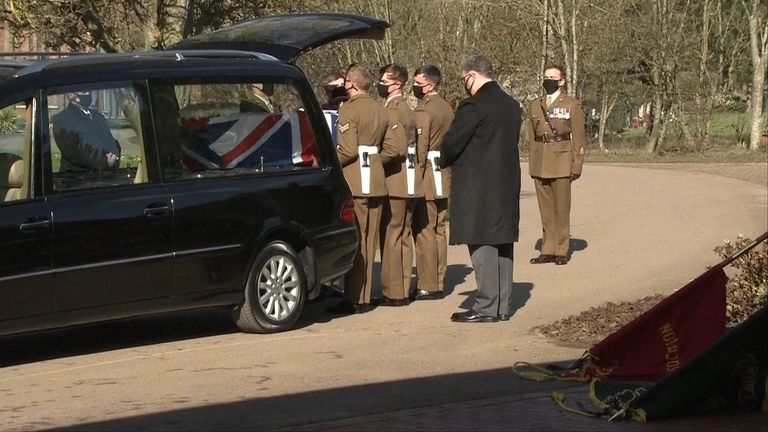 Soldiers lift Captain Sir Tom Moore's coffin from the hearse