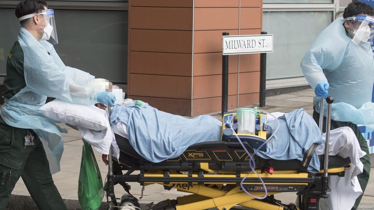 A patient is taken to an ambulance outside the Royal London Hospital in London