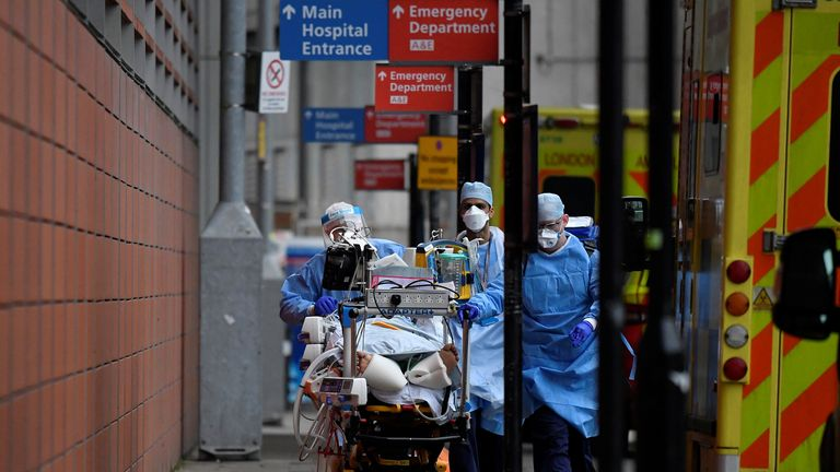 Medical workers move a patient between ambulances outside the Royal London Hospital