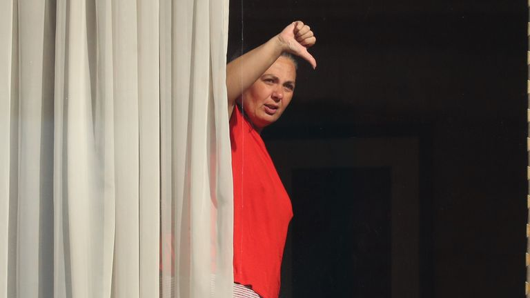 Andressa Pelosini, 43, waves to members of the media from the window of Radisson Blu Edwardian Hotel, near Heathrow Airport