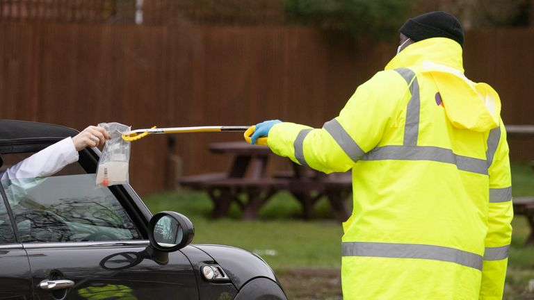 A coronavirus test is handed out of a car window in the car park in Hampshire