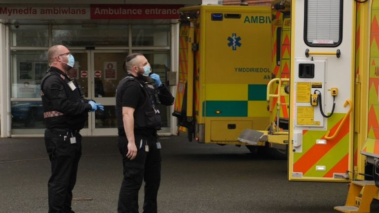 Hospital security staff wait for the paramedics to bring a mental health patient off their ambulance