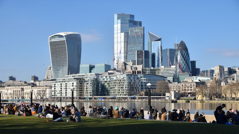 People enjoy the sunshine in Potters Fields Park with a view of the City of London skyline. The coronavirus alert level has dropped in England, prompting people to gather outside despite the lockdown restrictions still being in place across the country. (Photo by Vuk Valcic / SOPA Images/Sipa USA)