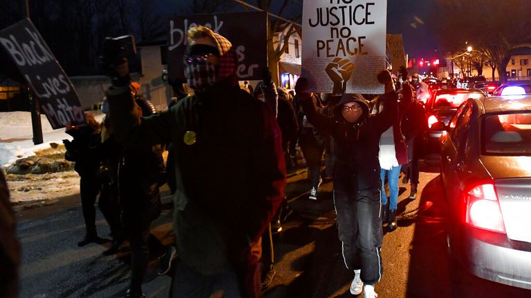 A crowd marches away from the site of Daniel Prude's fatal encounter with police officers a year ago. Pic: AP
